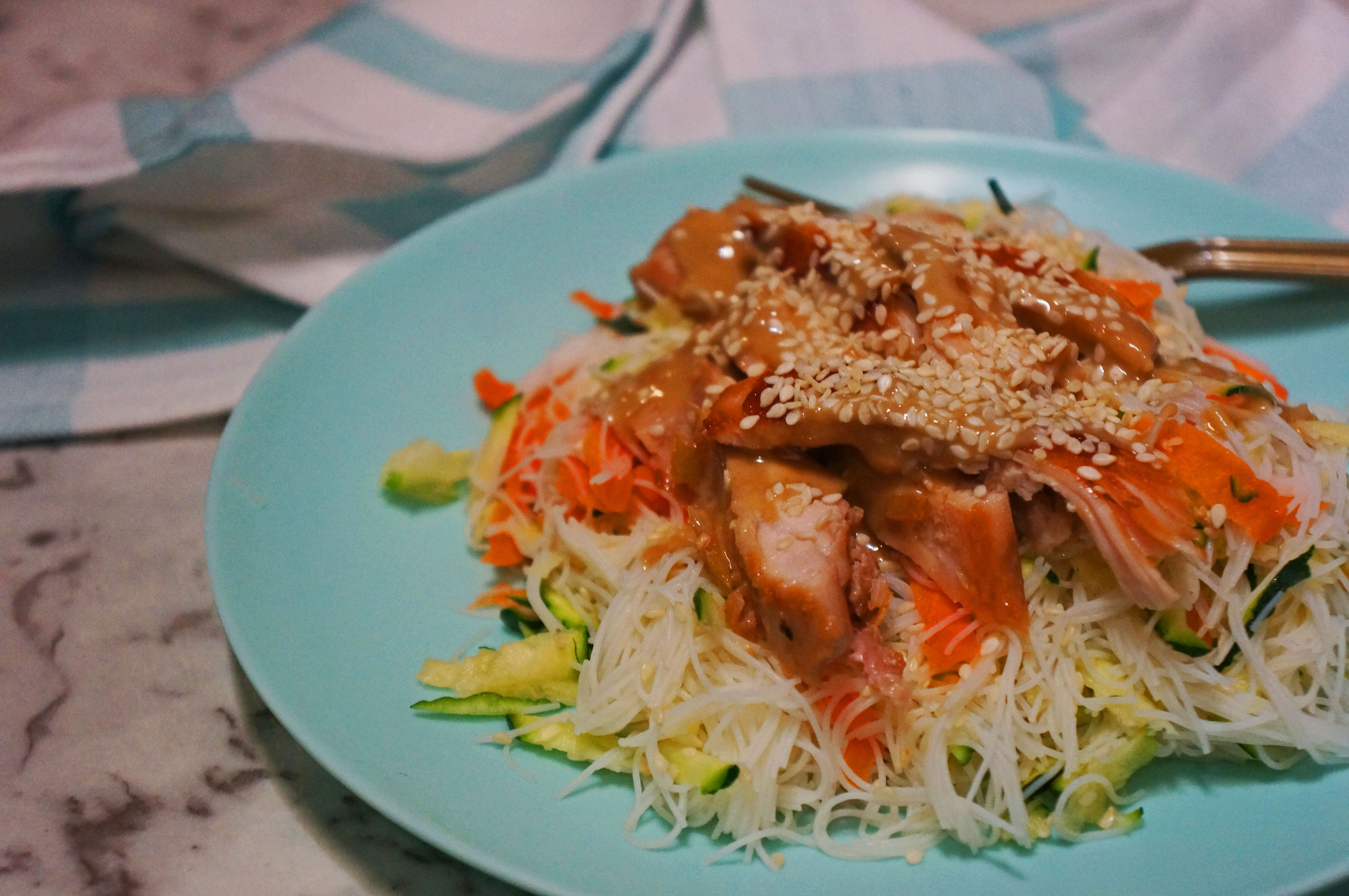 A tasty cold chicken noodle salad drizzled with sesame seeds and tahini
