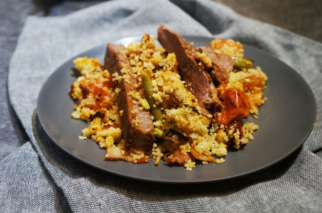 A paprika and garlic steak with crispy bacon couscous, green beans and tomatoes